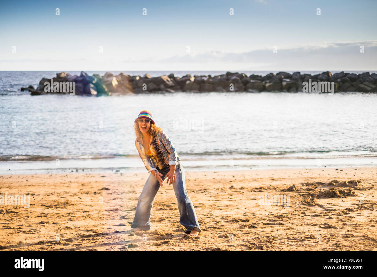 happy freedom crazy middle age woman jump on the beach for happiness and joyfun life outdoor vacation summer ocean and beach concept. fashion hippy cl - Stock Image