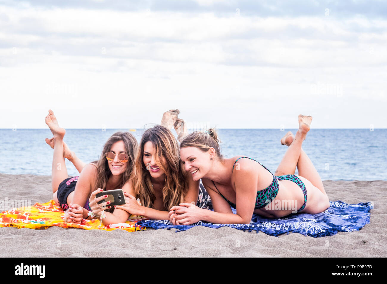 group of three beautiful girls in friendship stay lay down relaxed at the beach speaking and using a smartphone to share her summer lifestyle with fri - Stock Image