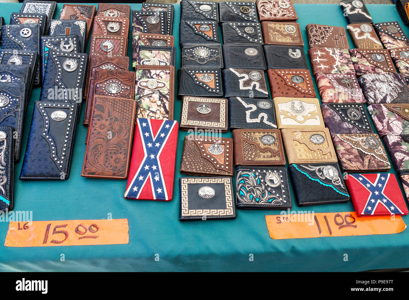 Florida Micanopy Fall Harvest Festival annual small town community event booths stalls vendors buying selling shopping tooled painted leather wallets - Stock Image