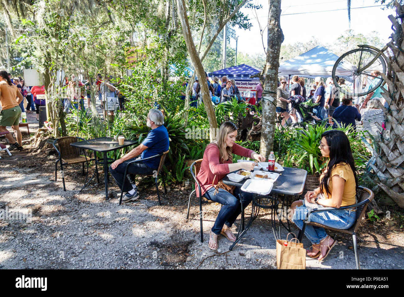 Florida Micanopy Fall Harvest Festival annual small town community event booths stalls vendors buying selling shade table eating woman friends - Stock Image