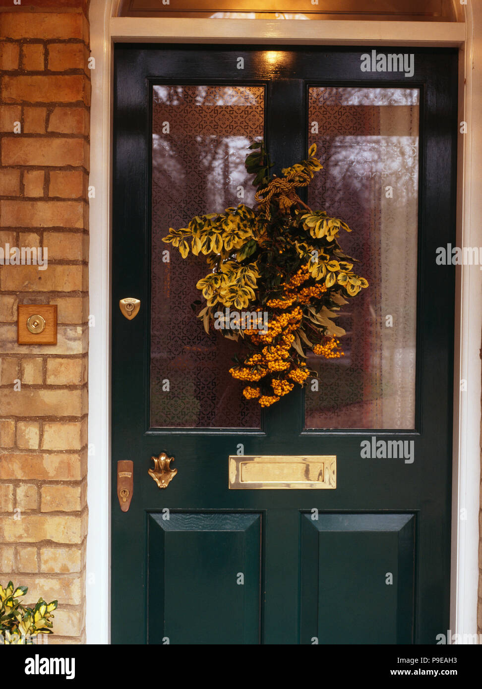 Close Up Of Half Glazed Front Door Decorated For Christmas With