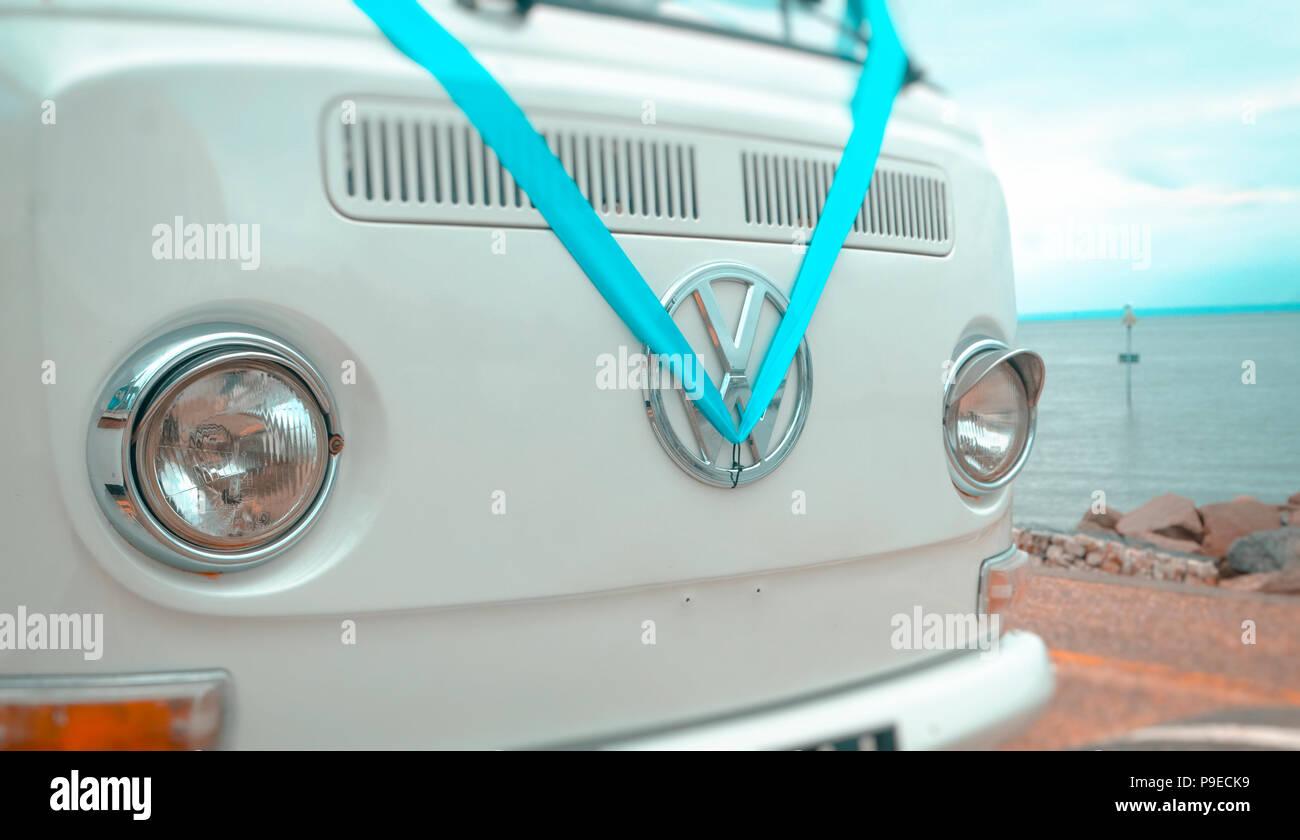 Volkswagen VW Badge on a camper van dressed in a blue wedding ribbon. - Stock Image