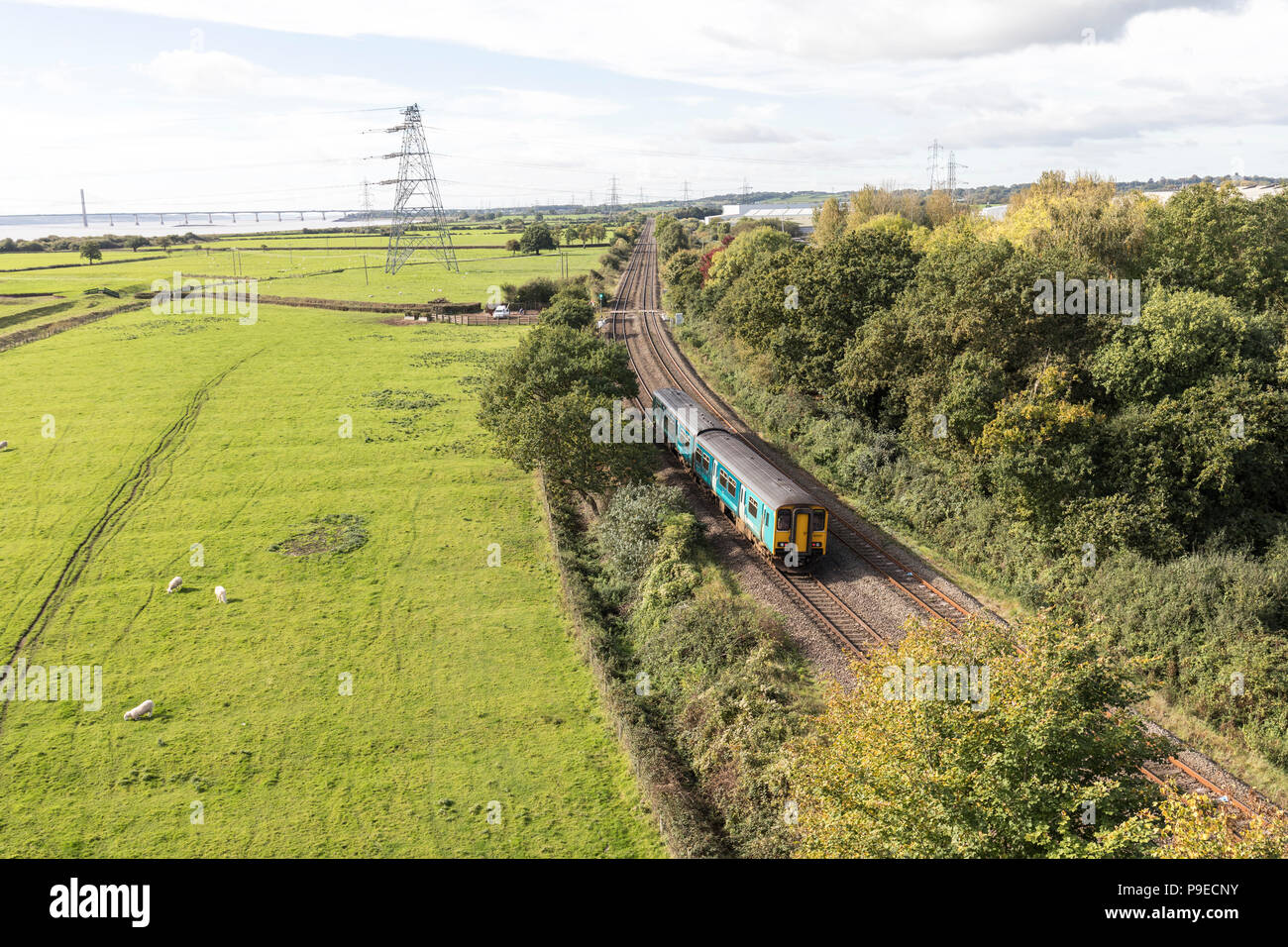 Railway alongside river Severn with road bridge in distance at Chepstow, Wales, UK - Stock Image