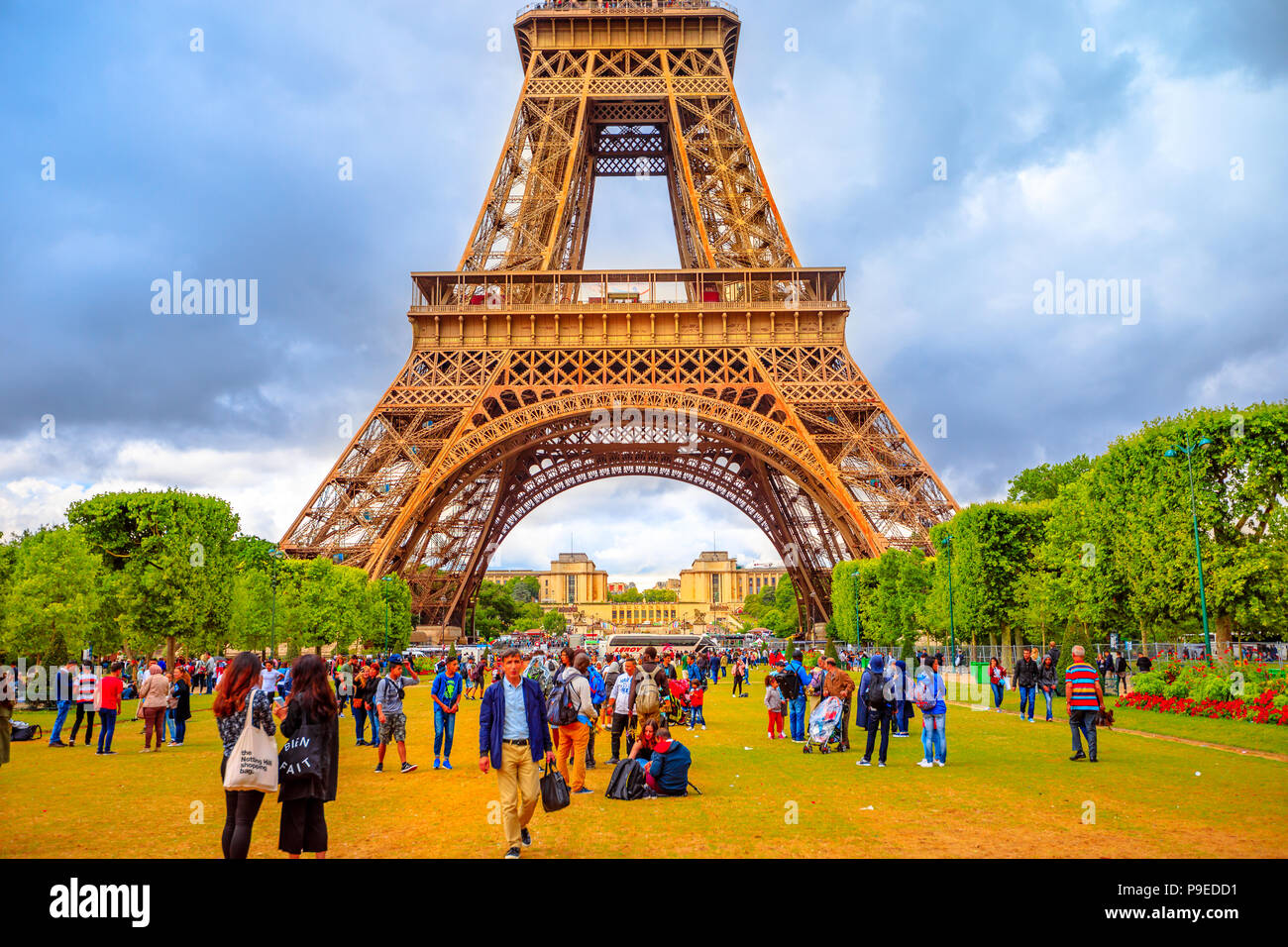 Paris, France - July 1, 2017: many people on Champ de Mars looking the Tour Eiffel, icon and symbol of Paris. Cloudy sky in a summer day. Europe travel concept. - Stock Image