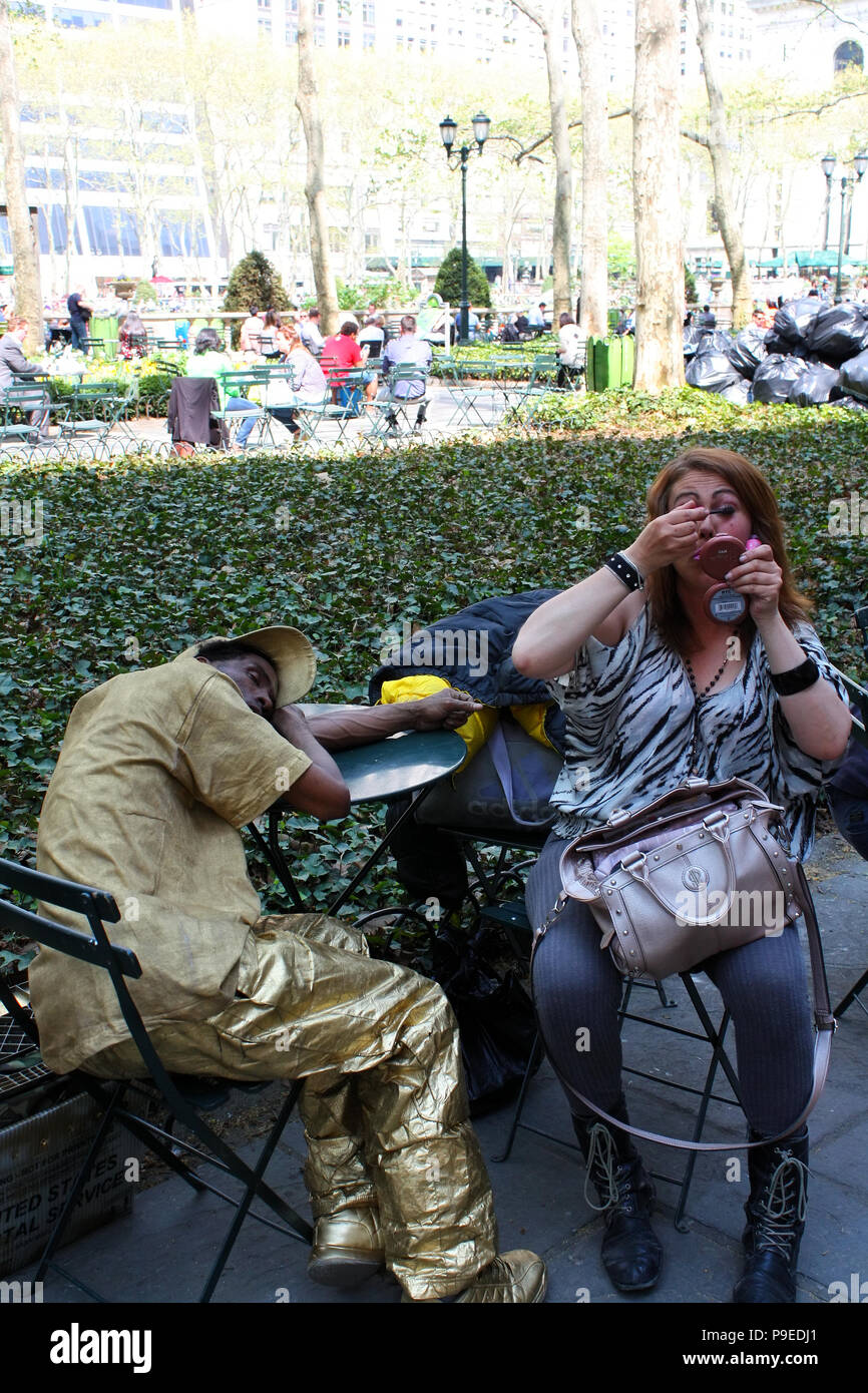 NEW YORK, NY - MAY 4: Odd couple. Woman puts makeup besides a man in an unusual outfit resting asleep at the park table in Bryant Park, Manhattan on M - Stock Image
