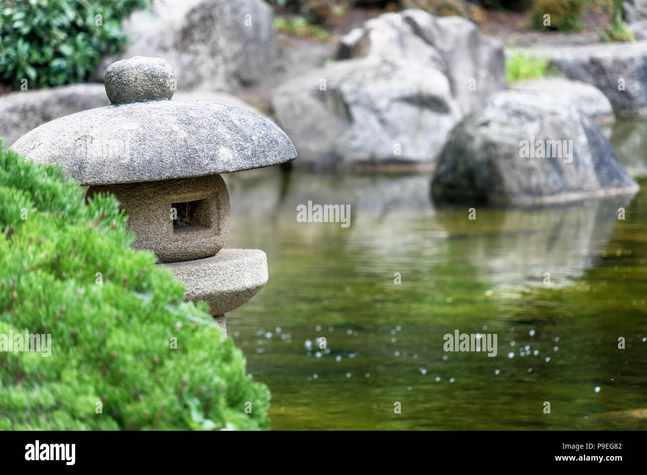 Pond in a Japanese garden with a traditional stone lantern in the foreground, low depth of field - Stock Image