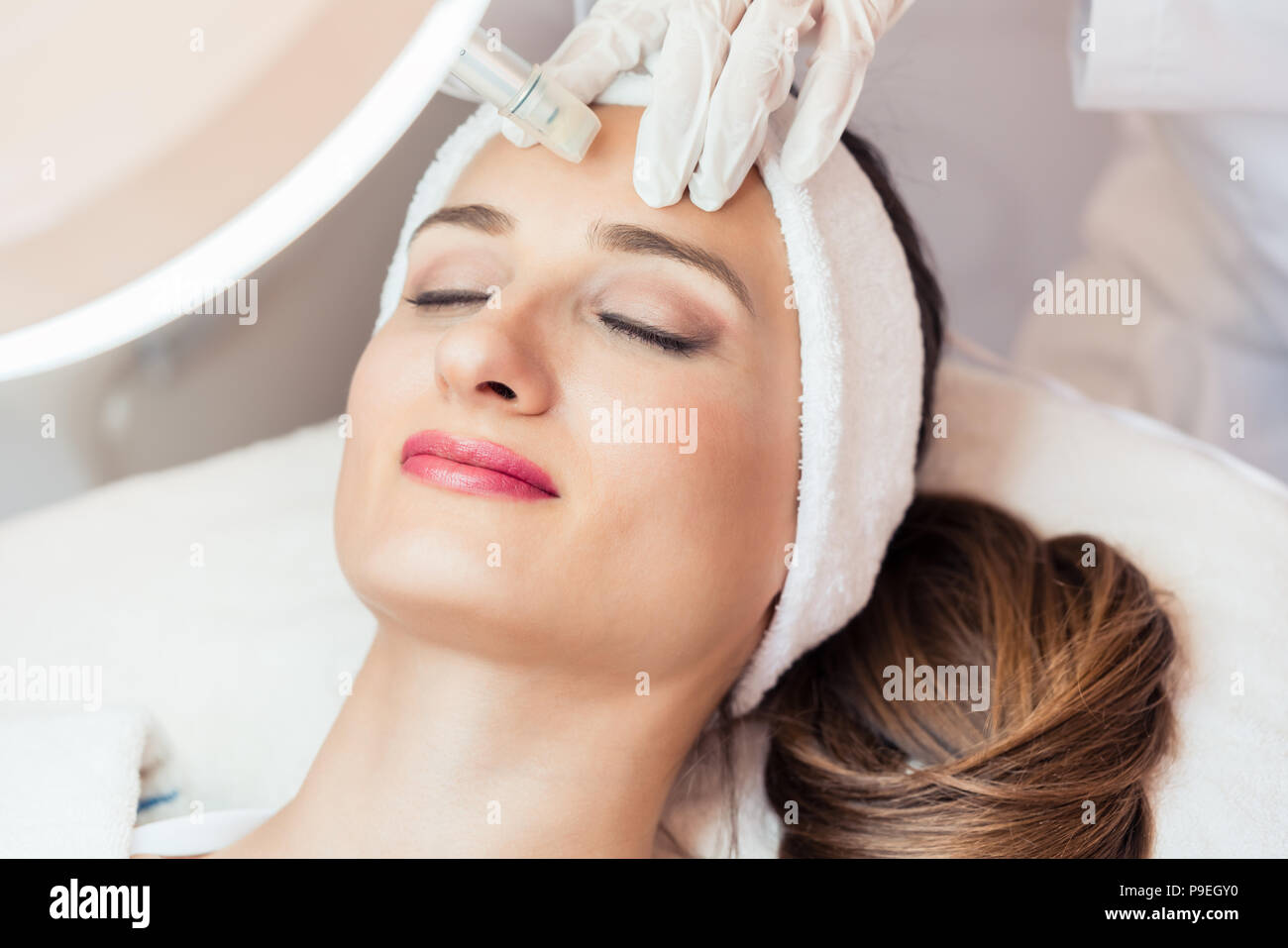 Close-up of the face of a woman relaxing during non-surgical facial treatment Stock Photo