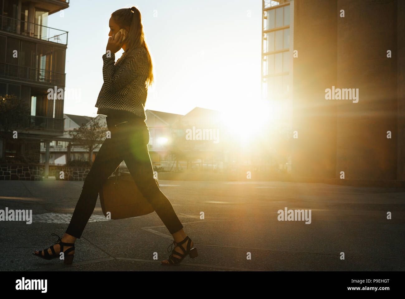 Businesswoman commuting to office early in the morning talking over mobile phone. Woman carrying handbag walking on city street to office. - Stock Image