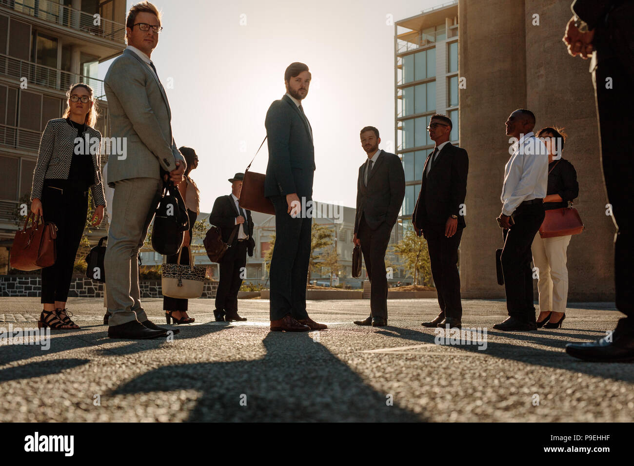 Business people looking at camera. Office going people standing on a busy street with sun flare in the background. - Stock Image