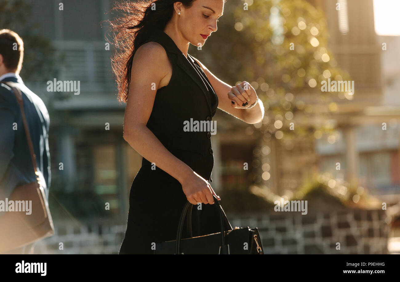 Woman looking at her wrist watch while commuting to office in the morning carrying her bag. Office going people walking on a street in the morning. - Stock Image