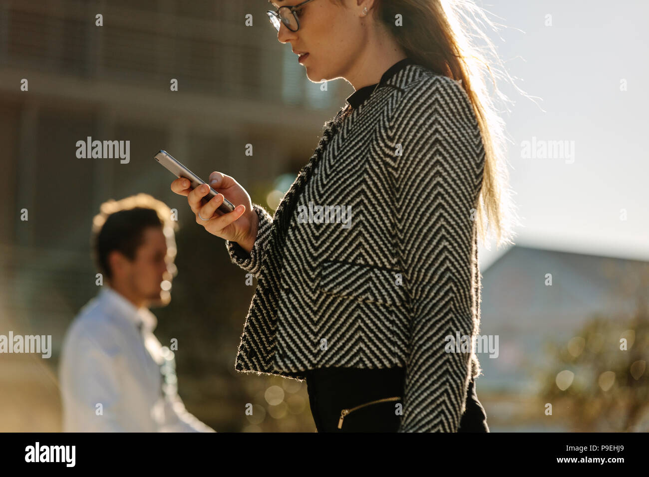 Woman looking at her mobile phone while walking on street to office. Busy office going woman walking on street and using her mobile phone with sun fla - Stock Image