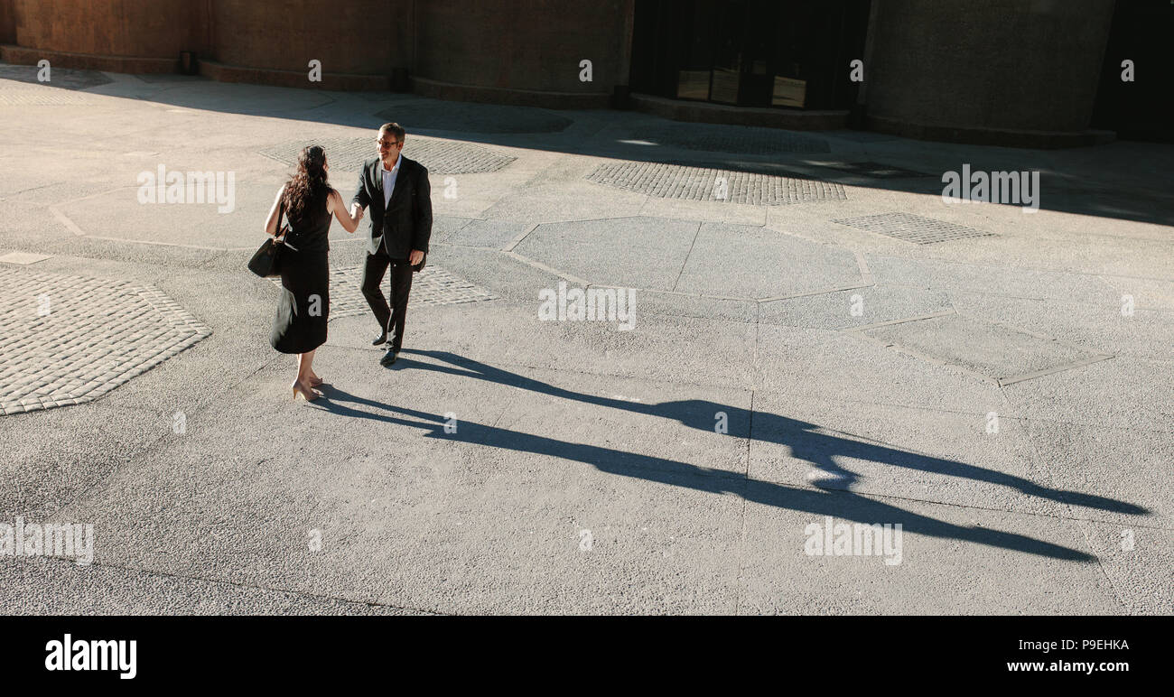 Business people greeting each other and shaking hands on a street while commuting to office. Businesswoman shaking hand with a colleague outdoors with - Stock Image
