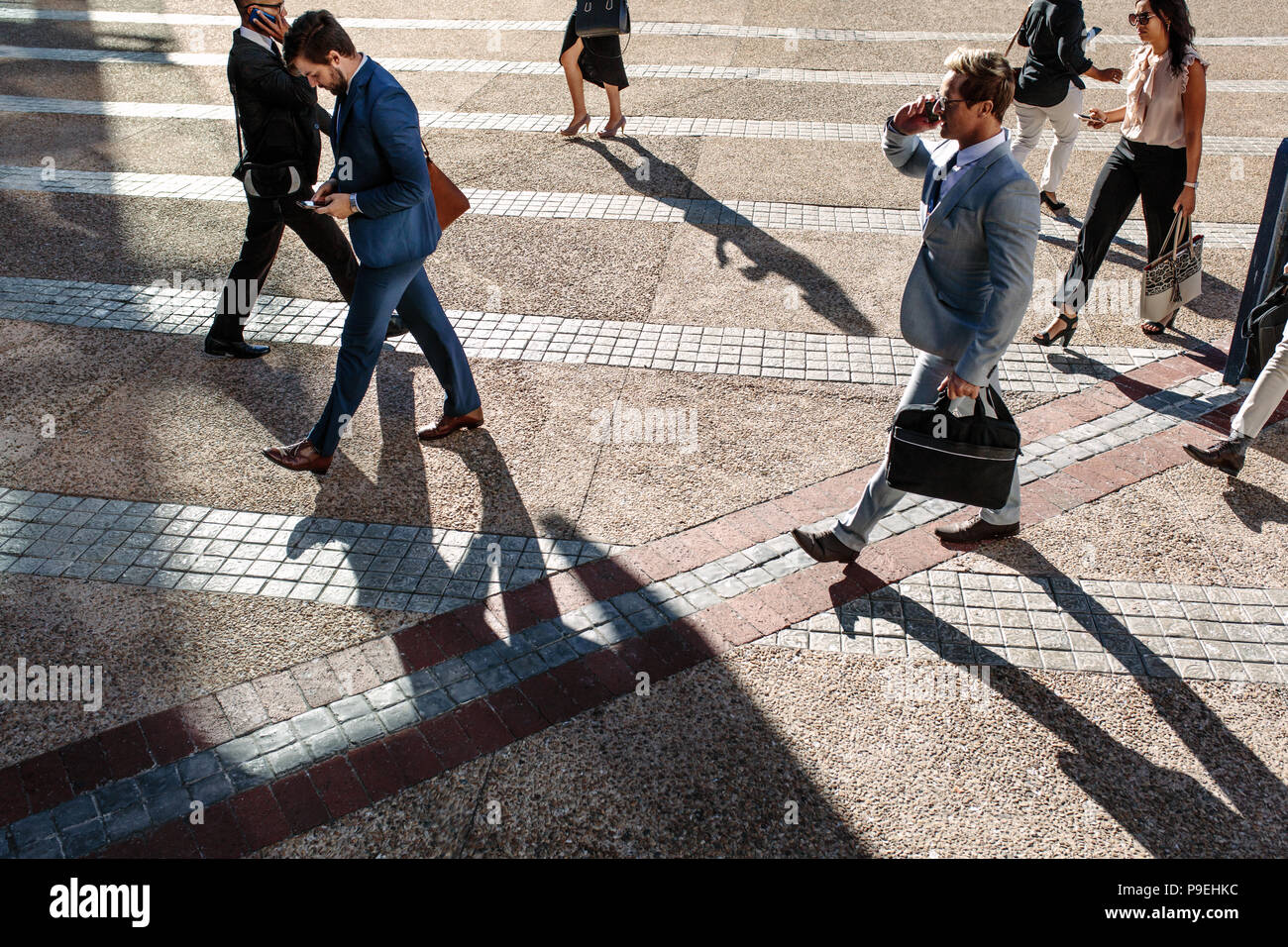 Business people commuting to office in the morning carrying office bags and using mobile phones. Businessmen and businesswomen in a hurry to reach off - Stock Image
