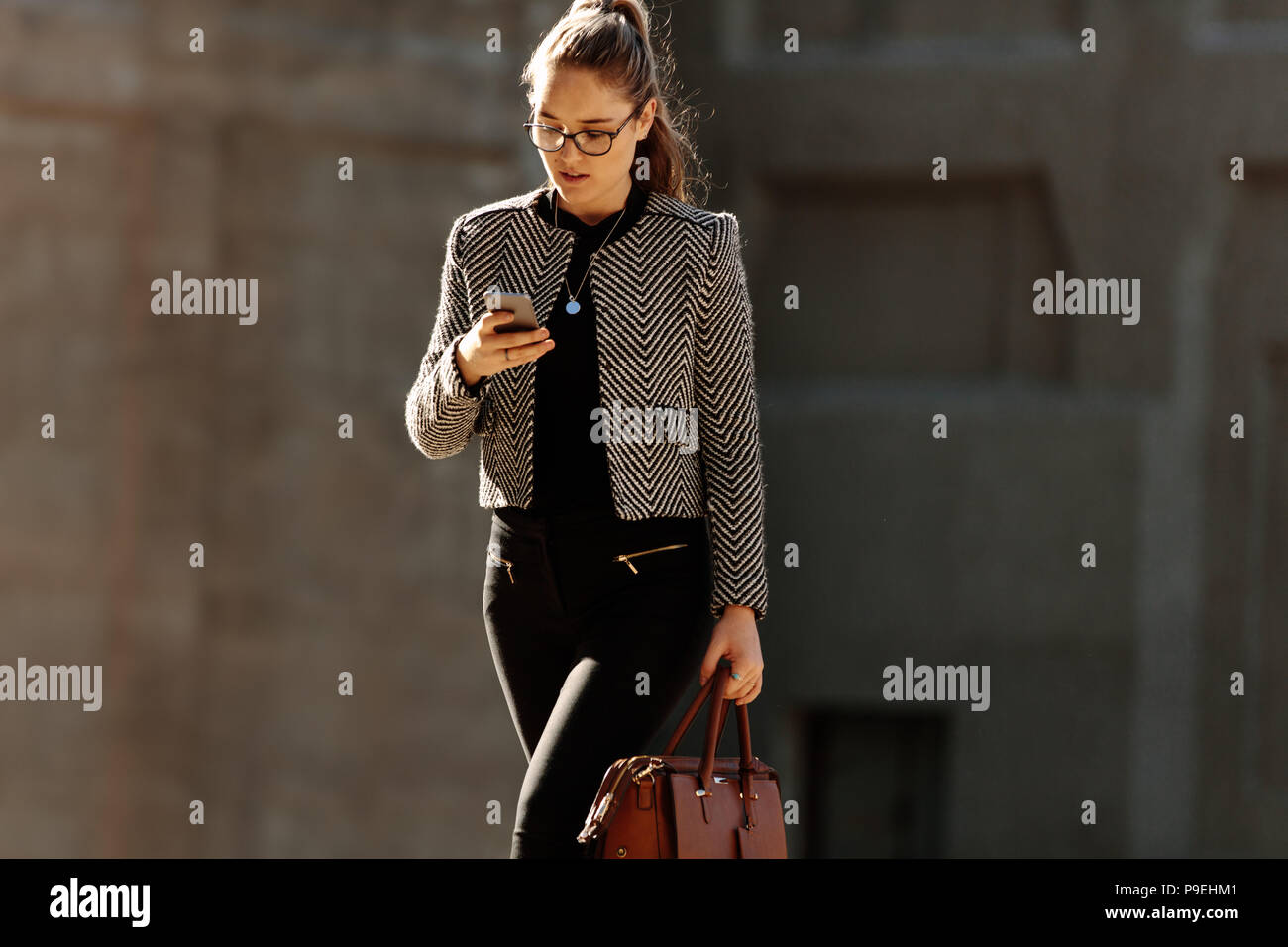 Businesswoman looking at her mobile phone while walking to office in the morning. Woman walking on city street to office carrying her office bag busy  - Stock Image