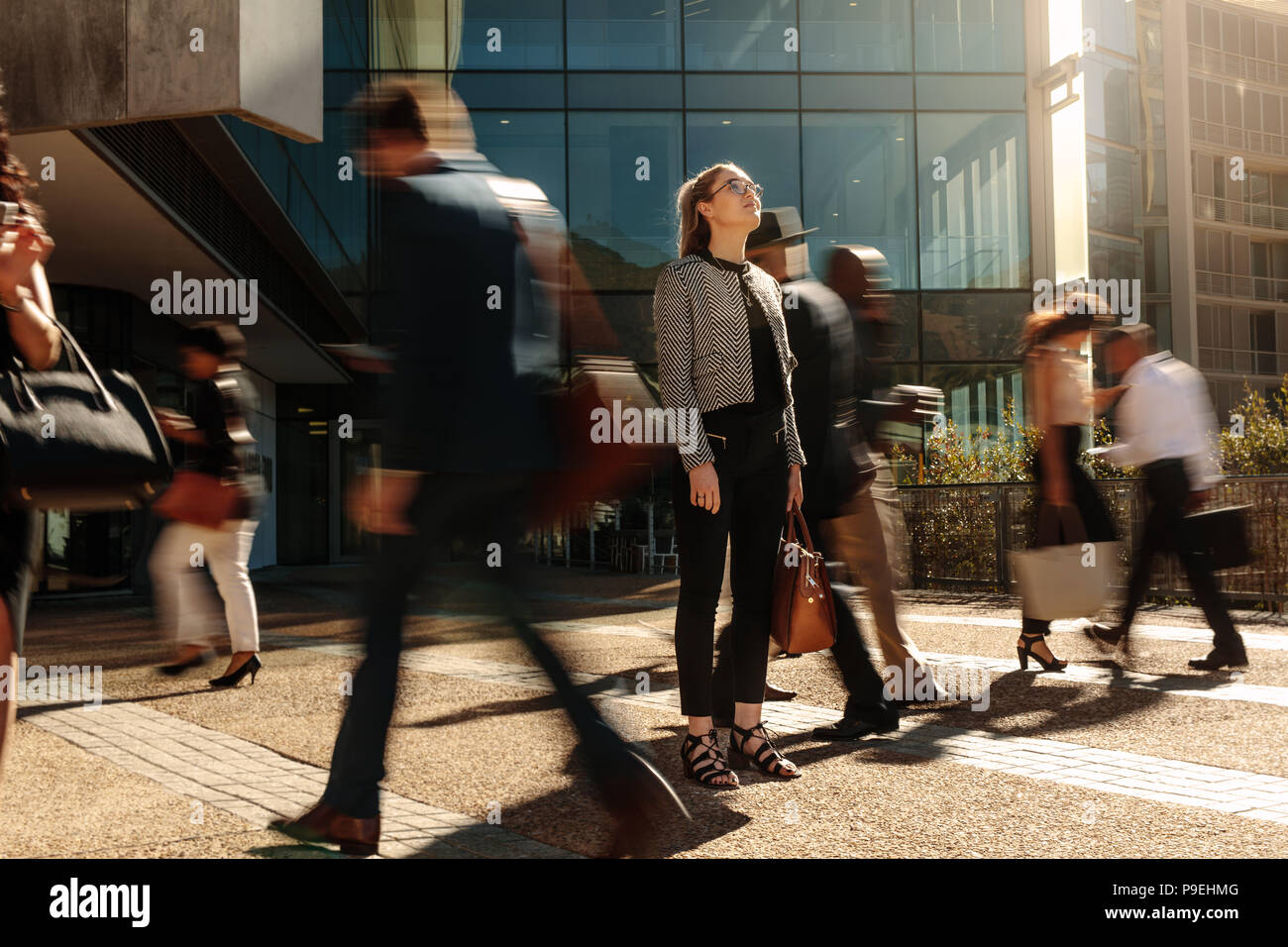 Woman standing amidst a busy office going crowd hooked to their mobile phones. Businesswoman holding her hand bag standing still on a busy street with Stock Photo