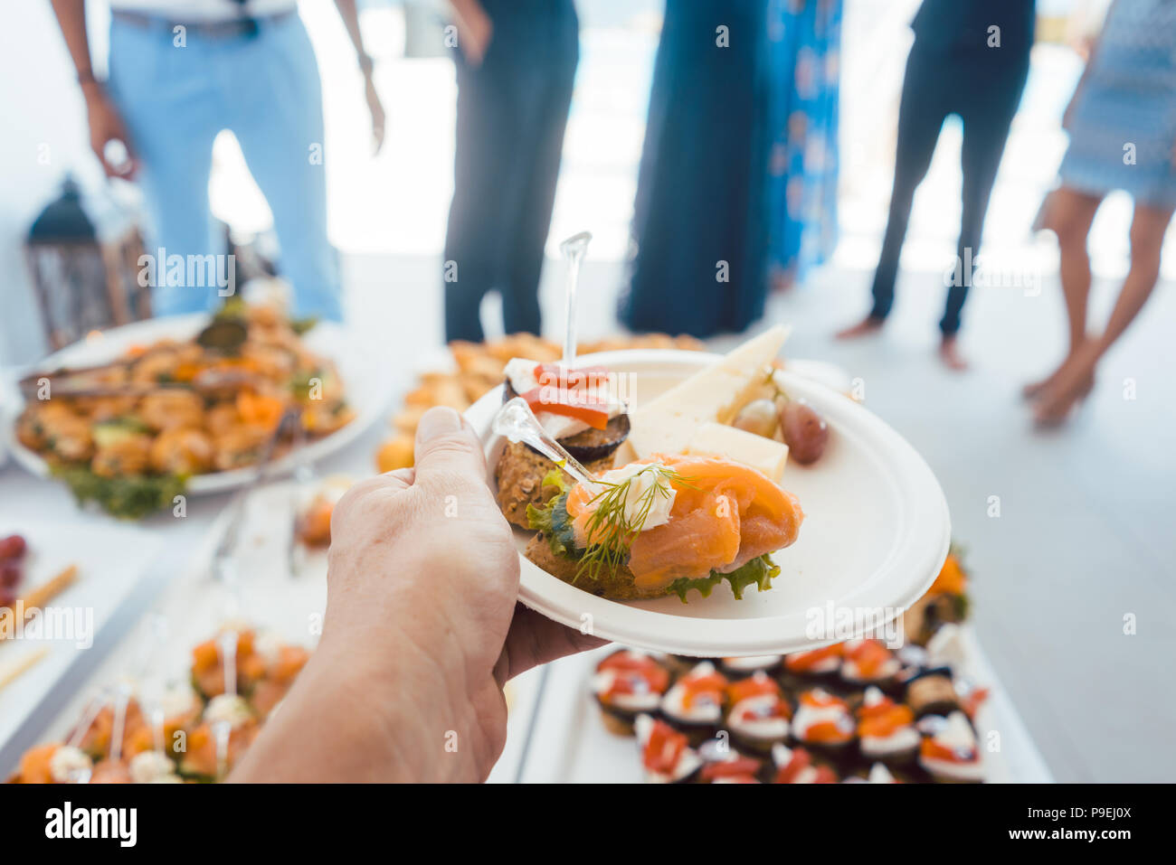 Man helping himself on Buffet of party outdoors taking food  - Stock Image
