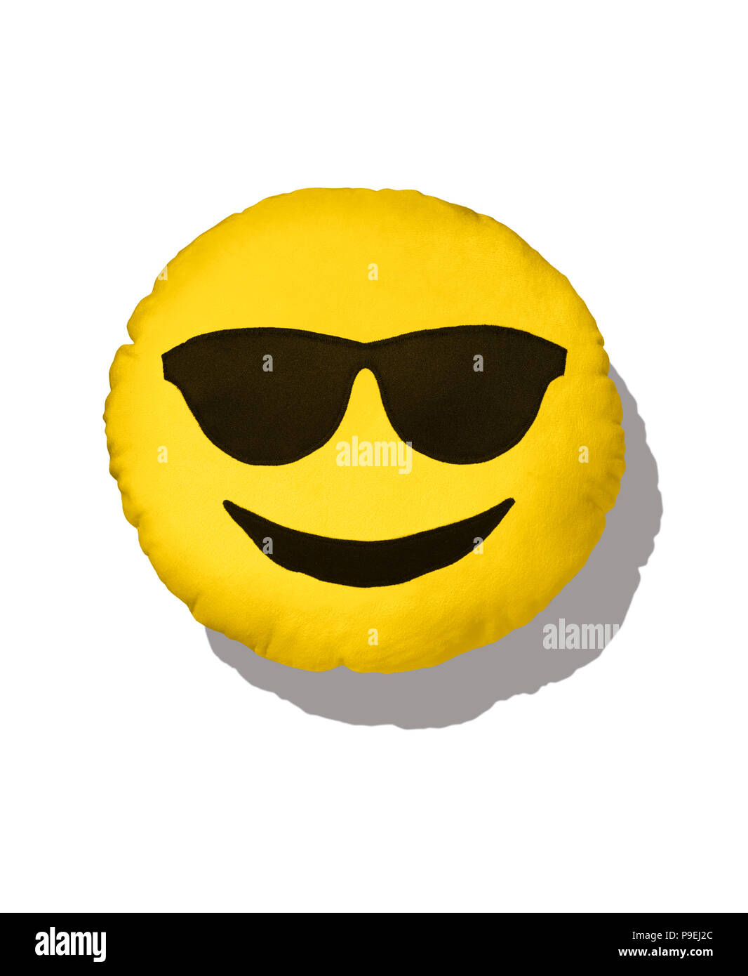 A colourful shot of the sunshine Emoji cushion with sun glasses. Stock Photo