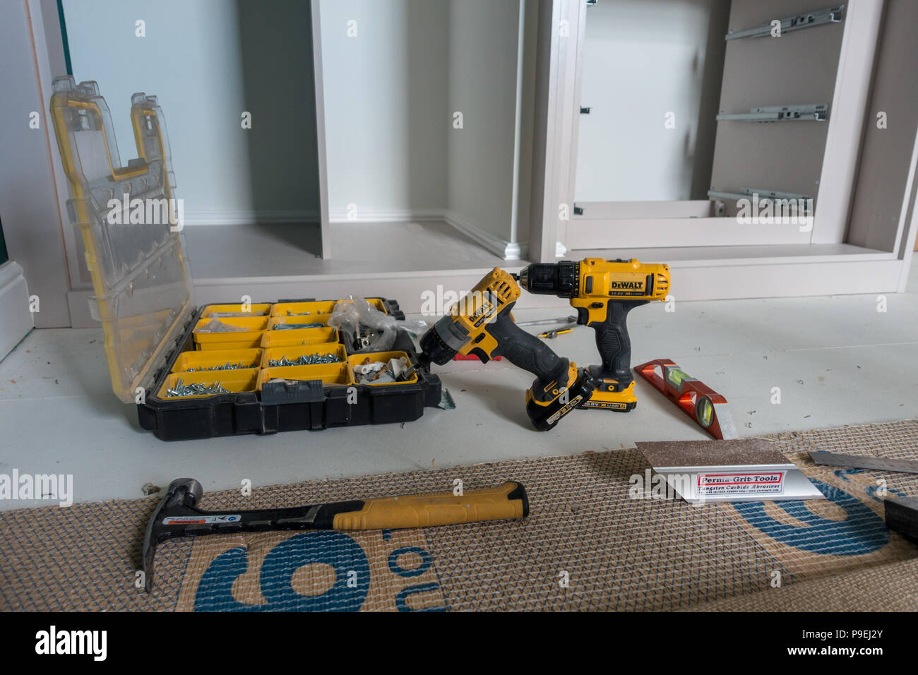 Home improvement tools on the floor next to a partially finished fitted wardrobe - Stock Image