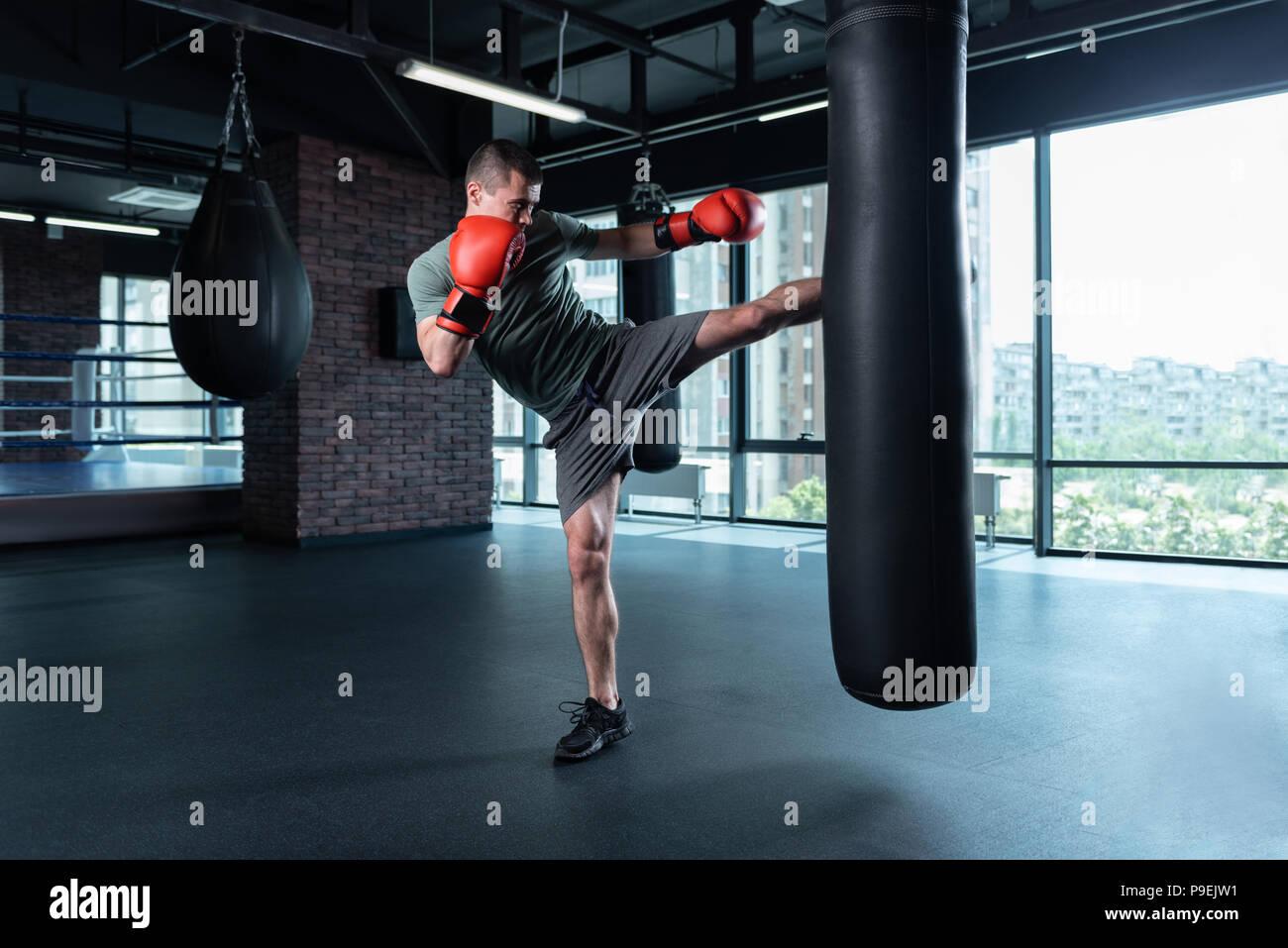 Athletic man wearing grey shorts lifting leg up - Stock Image