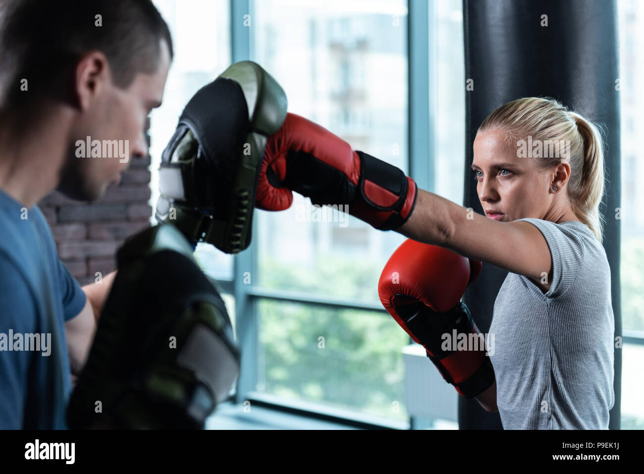 Blue-eyed woman having no prejudice while boxing with trainer - Stock Image