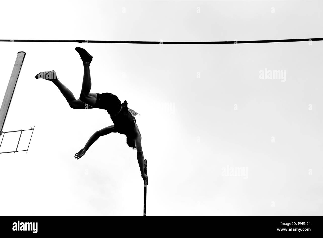 pole vault athlete pole vaulter jump in athletics black and white image - Stock Image
