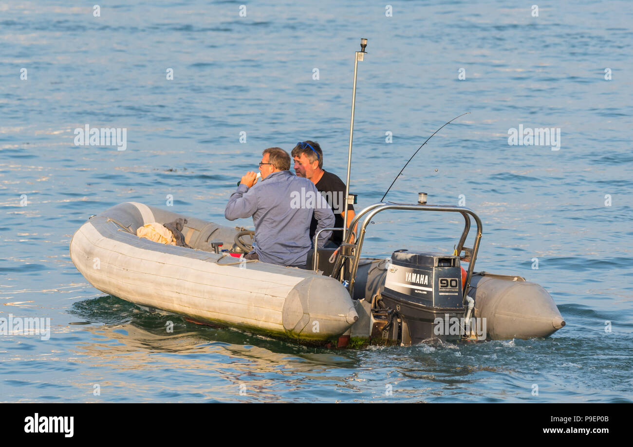 Pair of men in a rib with an outboard engine on water in the evening in Summer in the UK. - Stock Image