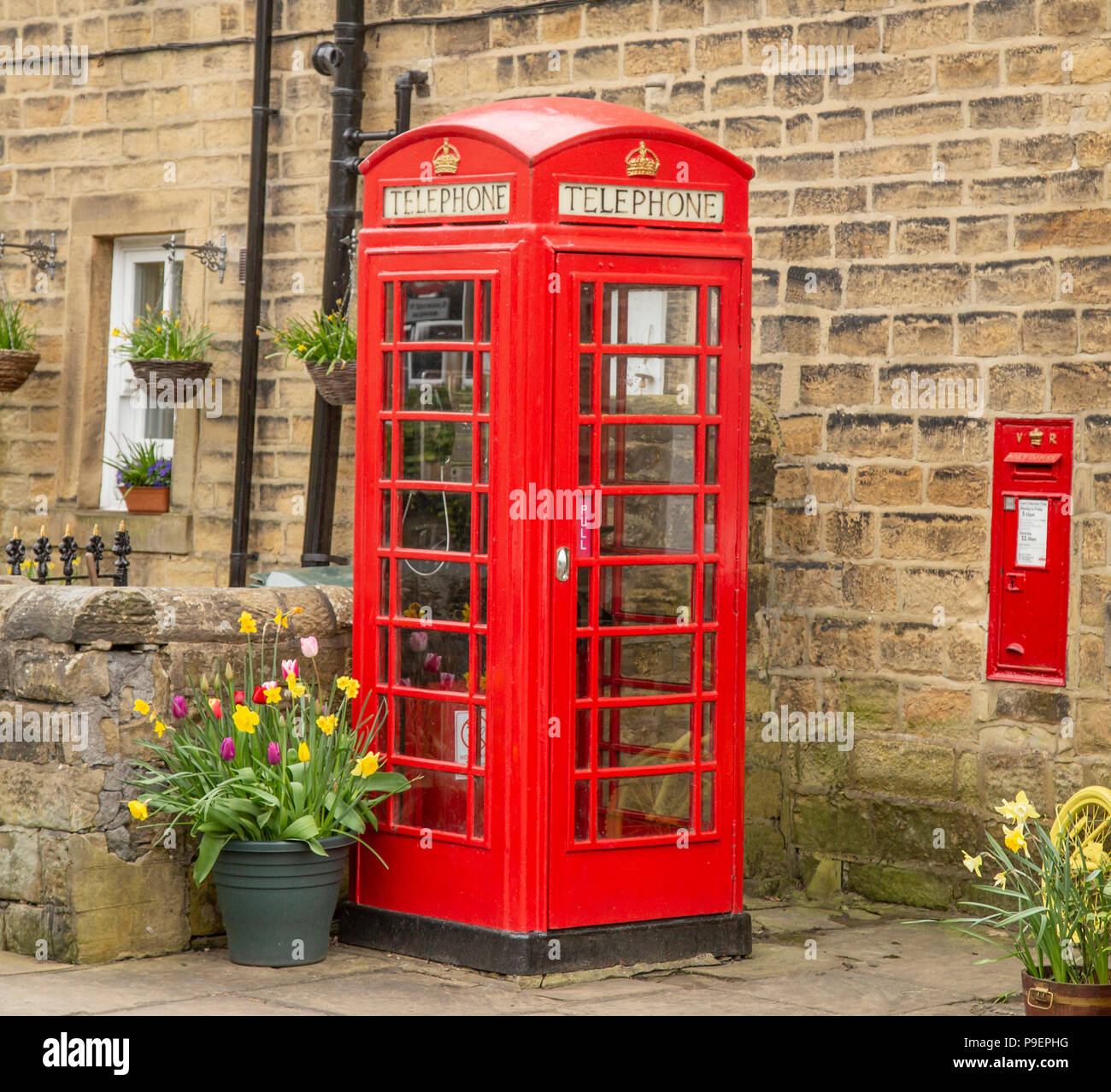 A K6 red telephone box (UK) and wall postbox in Esholt, West Yorkshire, England. - Stock Image