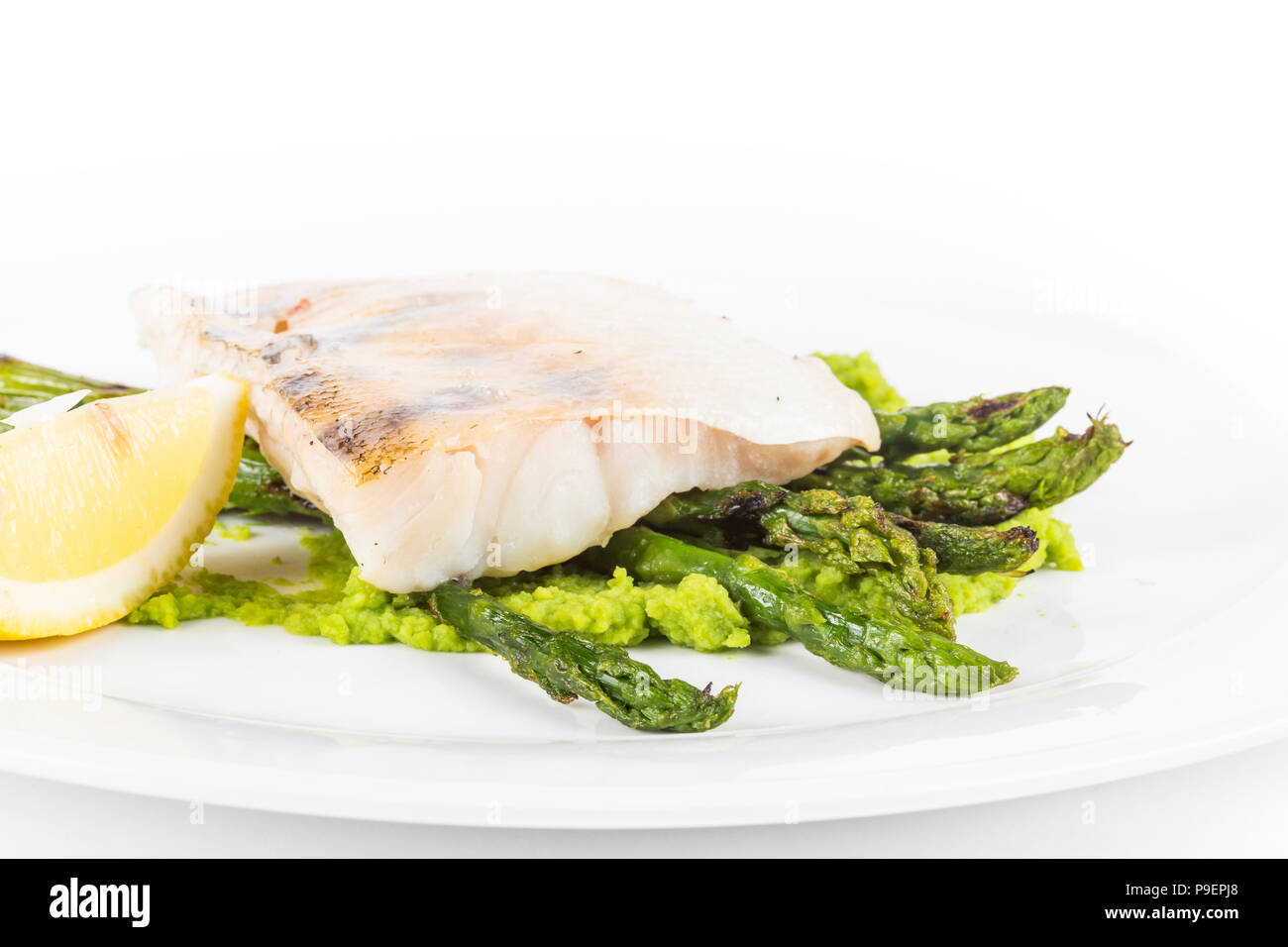 Steamed Fillet of Seabass with Green Peas Cream and Asparagus with lemon close up. Stock Photo