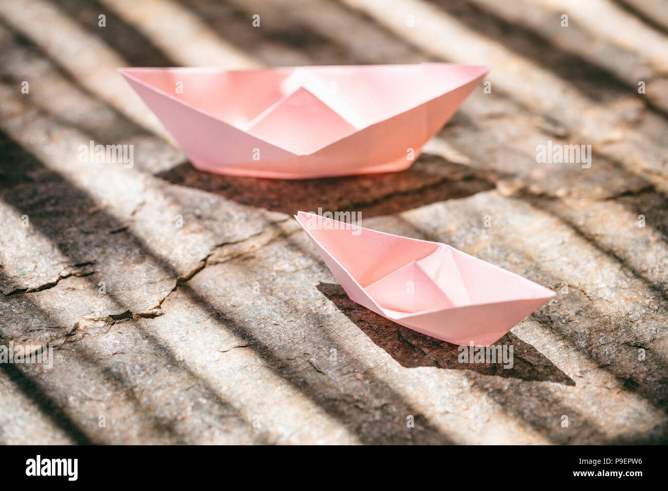 Two pink paper folded, origami, boats on a rock, copy space
