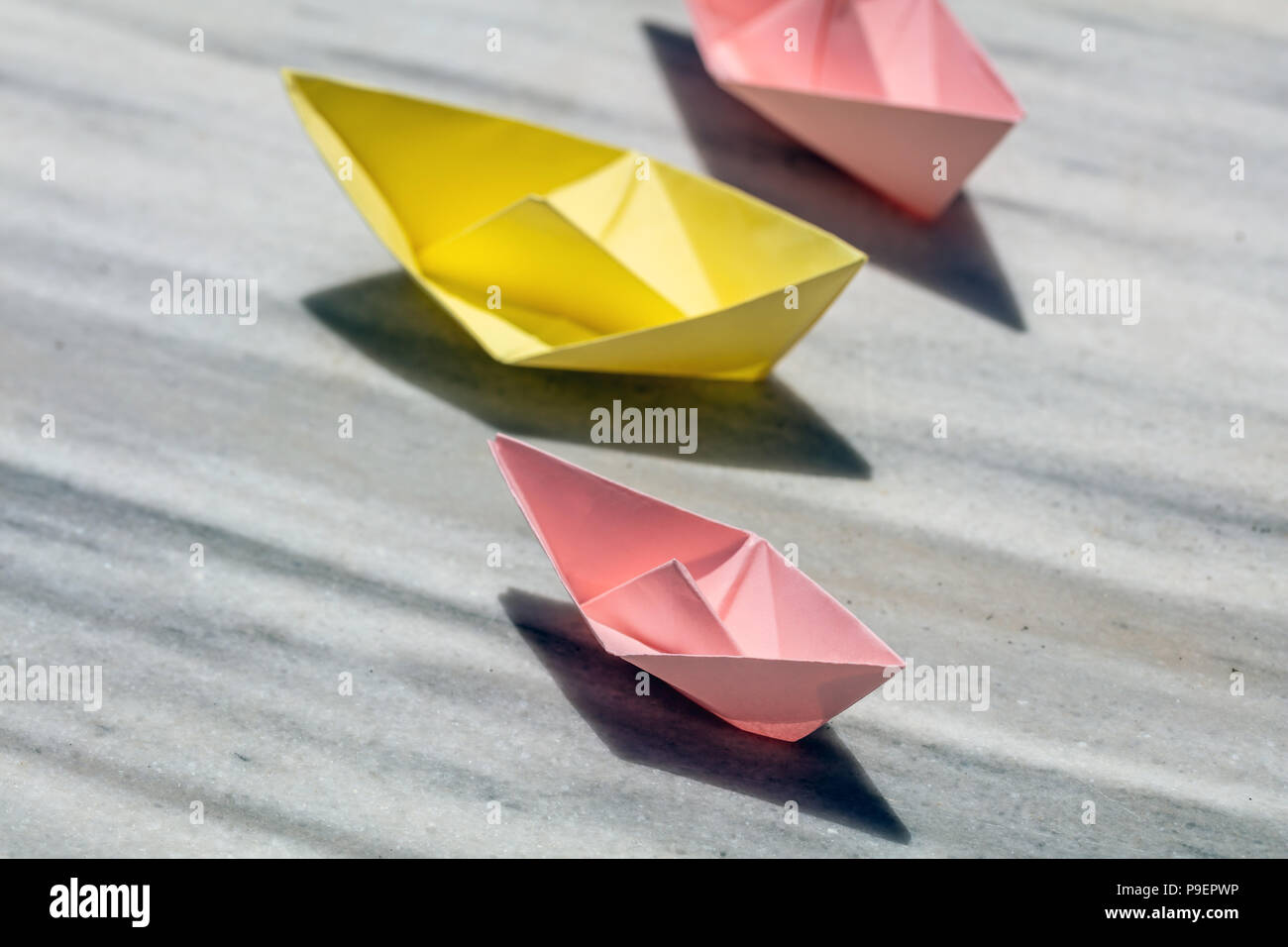 Pink and yellow paper folded, origami, boats on a rock, copy