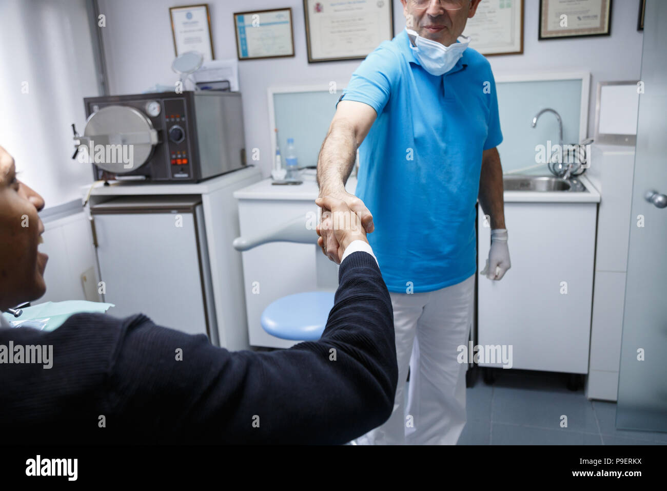 Young African-American man shaking hand of crop dentist having visit ...
