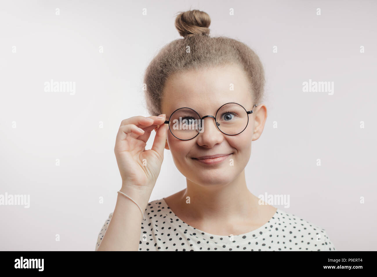 3731988cd498 young good-looking girl with blue eyes wearing round glasses isolated on  white background. touch glasses. kind teacher is full of enthusiasm.excited  s