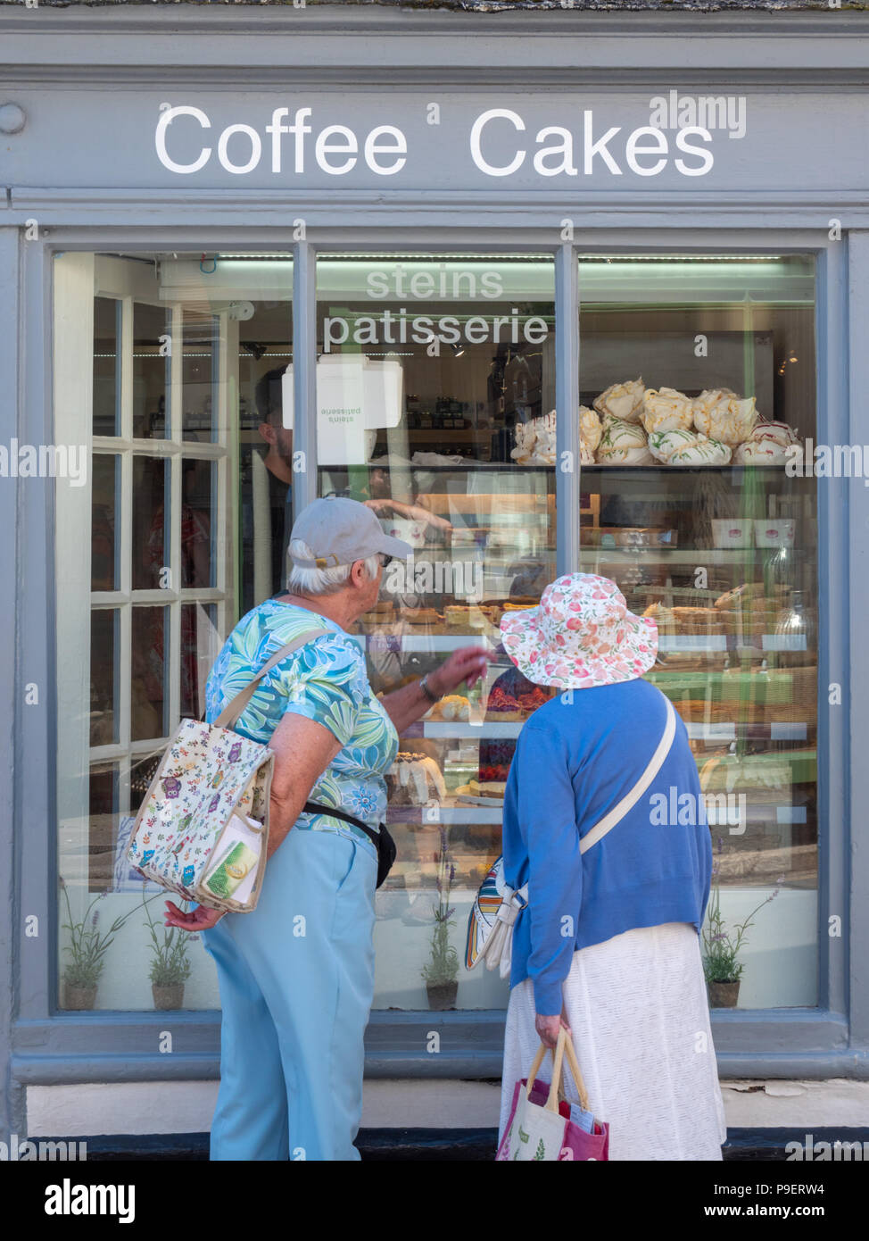 Two mature women shoppers looking in the window of Steins Patisserie and bakers shop in Padstow Cornwall UK - Stock Image