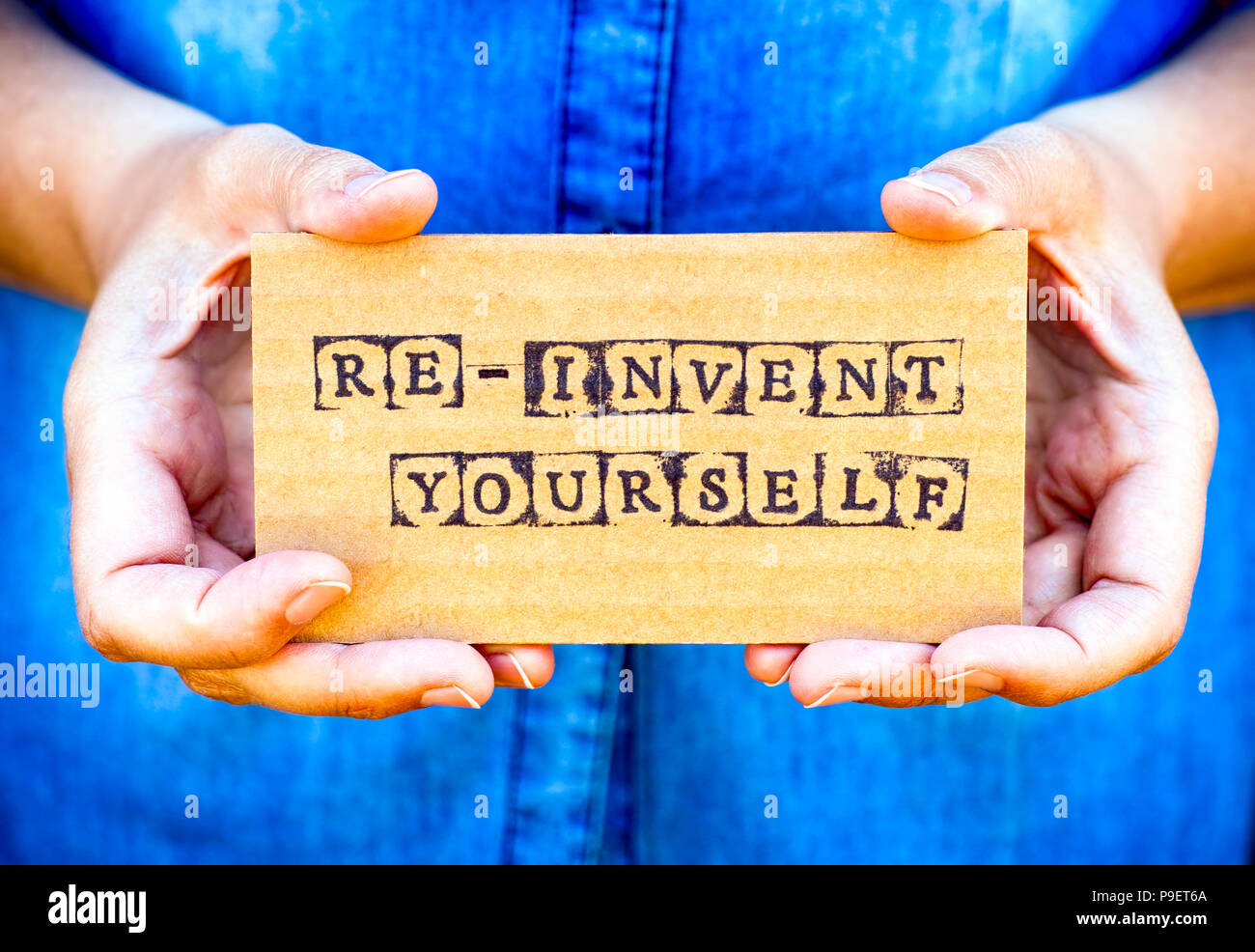 Woman hand holding cardboard card with words Re-Invent Yourself made by black alphabet stamps. Denim backgrounds. - Stock Image