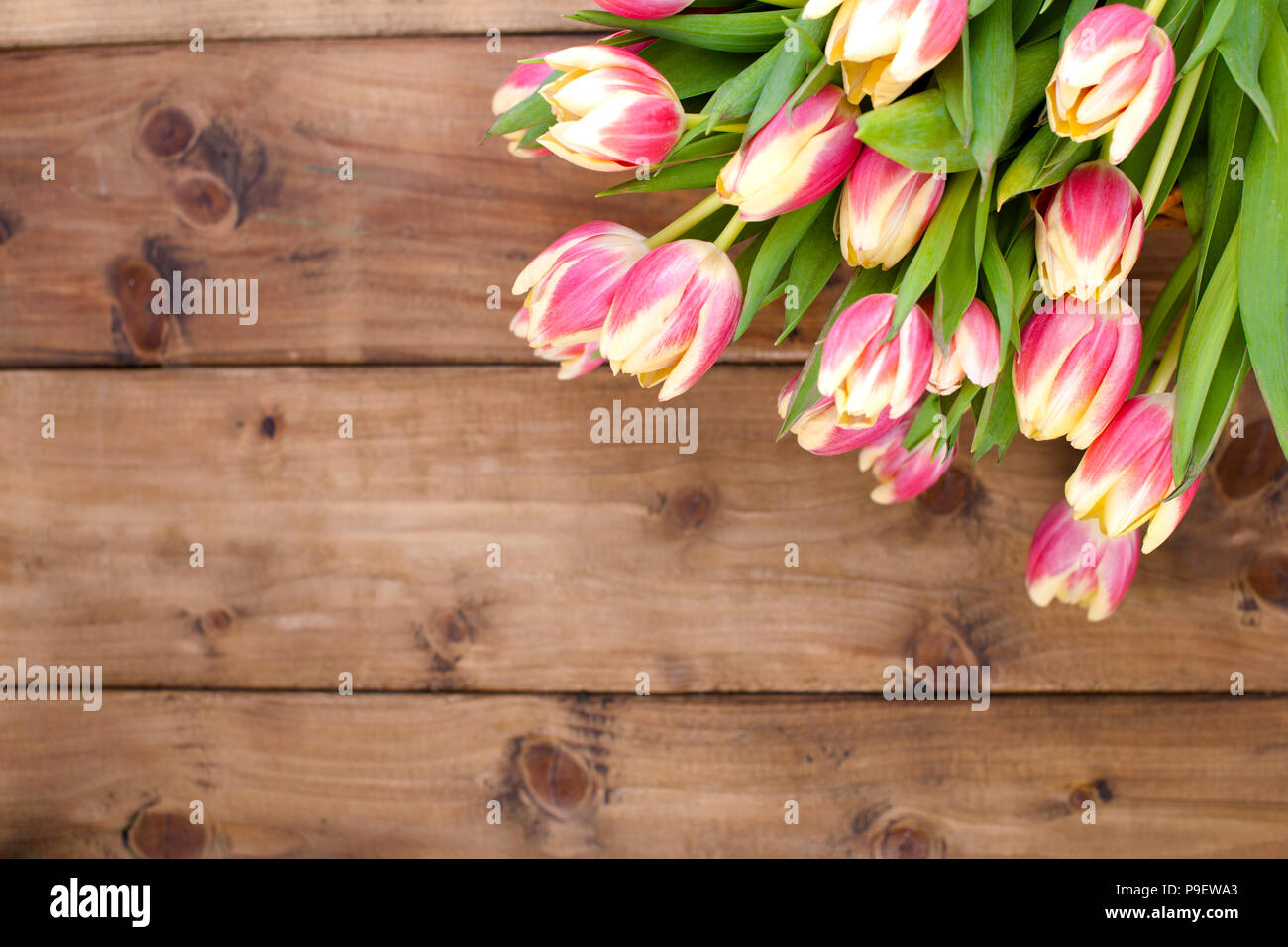 Beautiful bouquet of fresh spring flowers. Tulips. Wooden brown background. Free space for text or a postcard - Stock Image