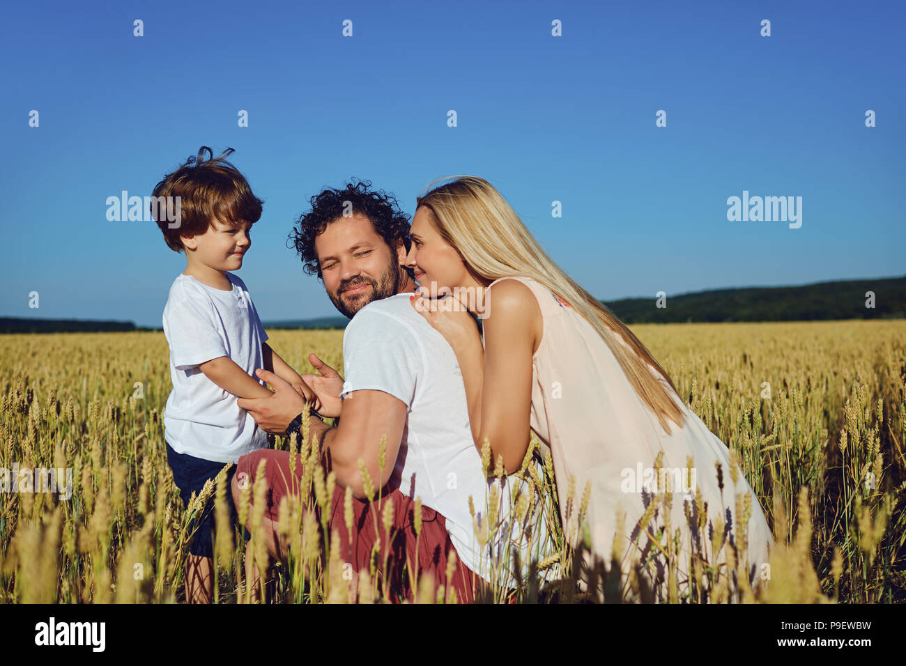 Happy family having fun playing  in the field. - Stock Image