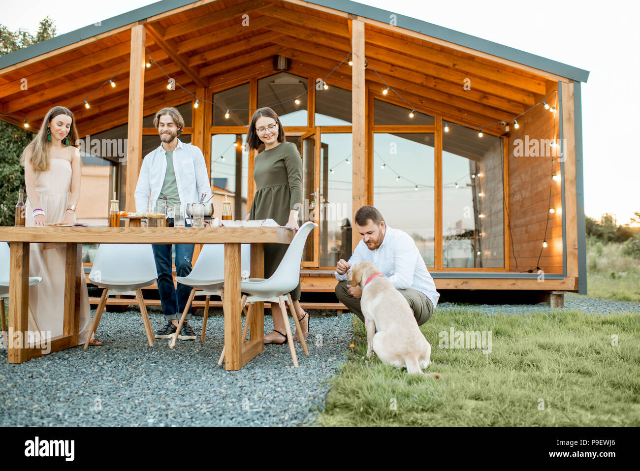 Friends with dog on the backyard of the house - Stock Image