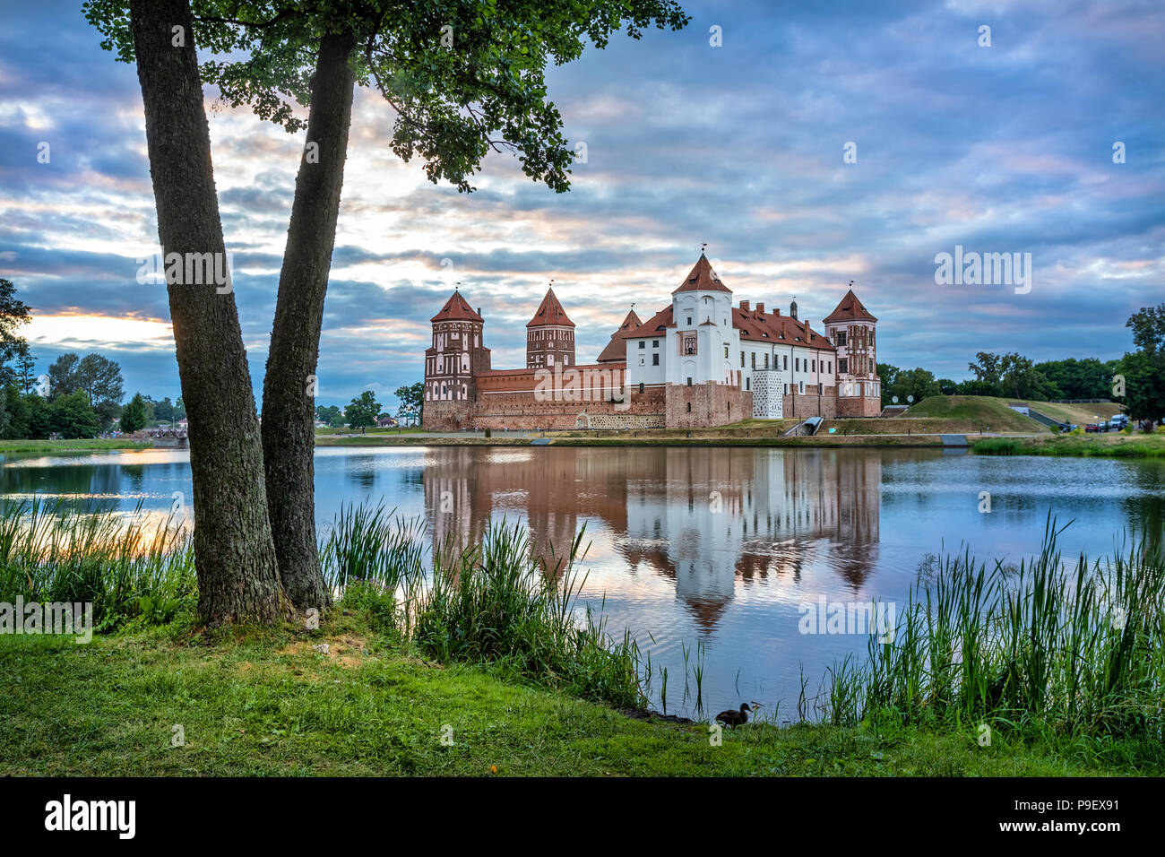 Mir Castle reflecting in water in the evening, Belarus - Stock Image