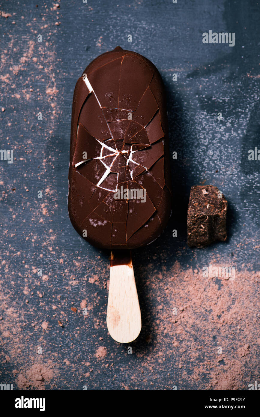 high angle view of a chocolate ice cream bar on a dark rustic wooden table sprinkled with cocoa powder - Stock Image