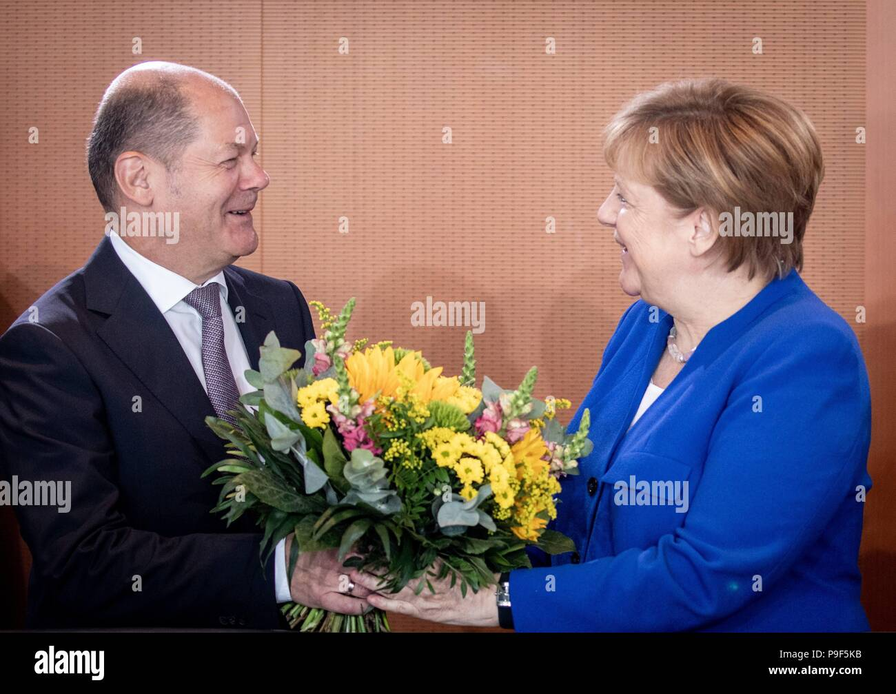 18 July 2018, Berlin, Germany: German chancellor Angela Merkel (CDU) receives a belated birthday bouqet from Olaf Scholz (SPD, L), federal minister of finance at the start of the federal cabinet meeting at the chancellery. Photo: Kay Nietfeld/dpa - Stock Image