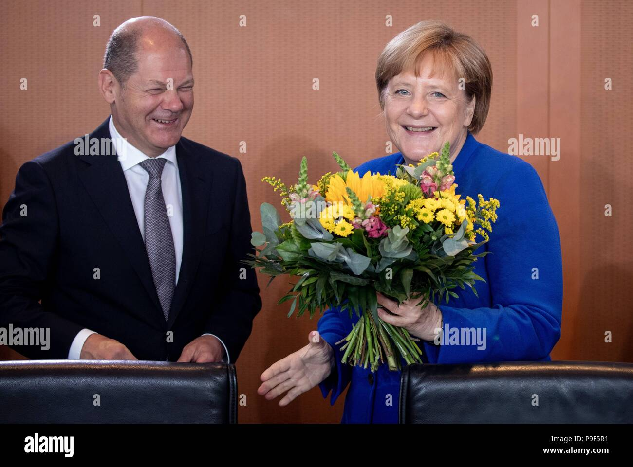 Berlin, Germany. 18th July, 2018. German chancellor Angela Merkel (CDU) receives a belated birthday bouqet from Olaf Scholz (SPD, L), federal minister of finance at the start of the federal cabinet meeting at the chancellery. Credit: Kay Nietfeld/dpa/Alamy Live News - Stock Image