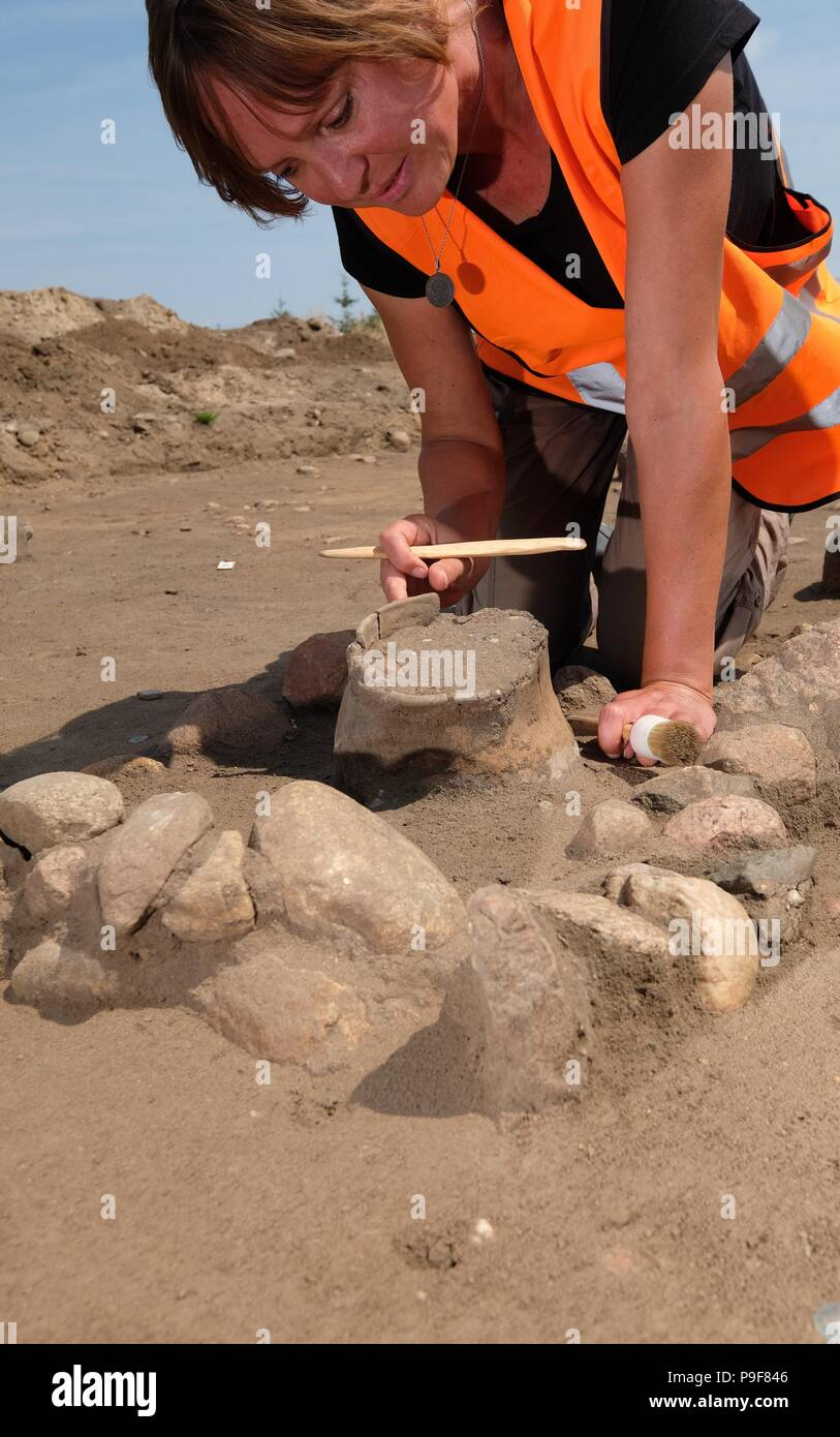 18 July 2018, Zerbst, Germany: Head of excavations Xandra Dalidowski works on an urn burial field from the older Iron Age in the district Leps. During construction works on gas piping graves from 750 B.C. were found, which are now under the inspection of the state office for the preservation of historical monuments Saxony-Anhalt. Photo: Sebastian Willnow/dpa-Zentralbild/dpa Stock Photo