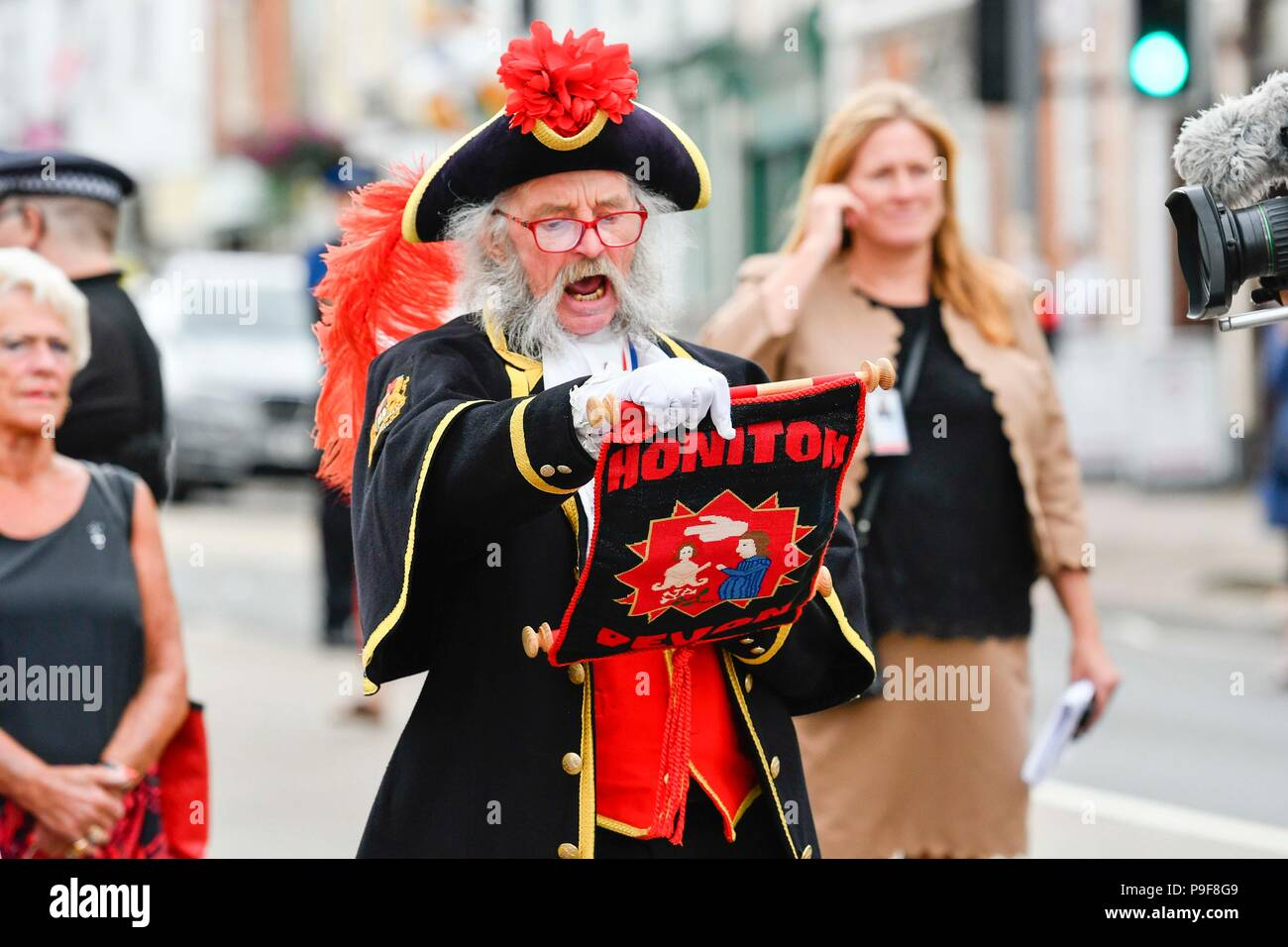 Honiton, Devon, UK.  18th July 2018.   The Duke and Duchess of Cornwall visit the Gate to Plate food market at Honiton in Devon.  Honiton town crier Dave Retter gives a rousing welcome cry.  Picture Credit: Graham Hunt/Alamy Live News Stock Photo