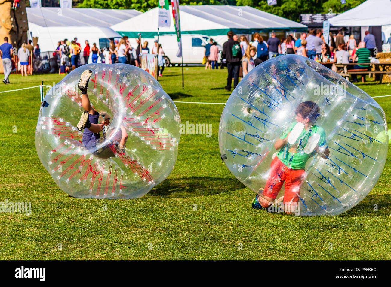 Two children playing in inflatable balls at Northumberland County Show, Stocksfield, Northumberland, UK. - Stock Image