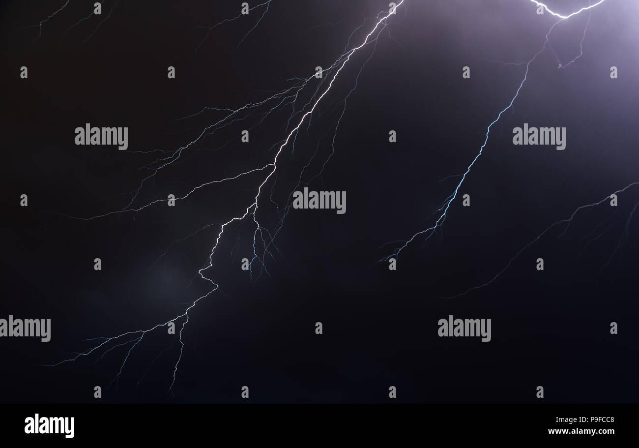 Night sky illuminated by lightning bolts - Stock Image