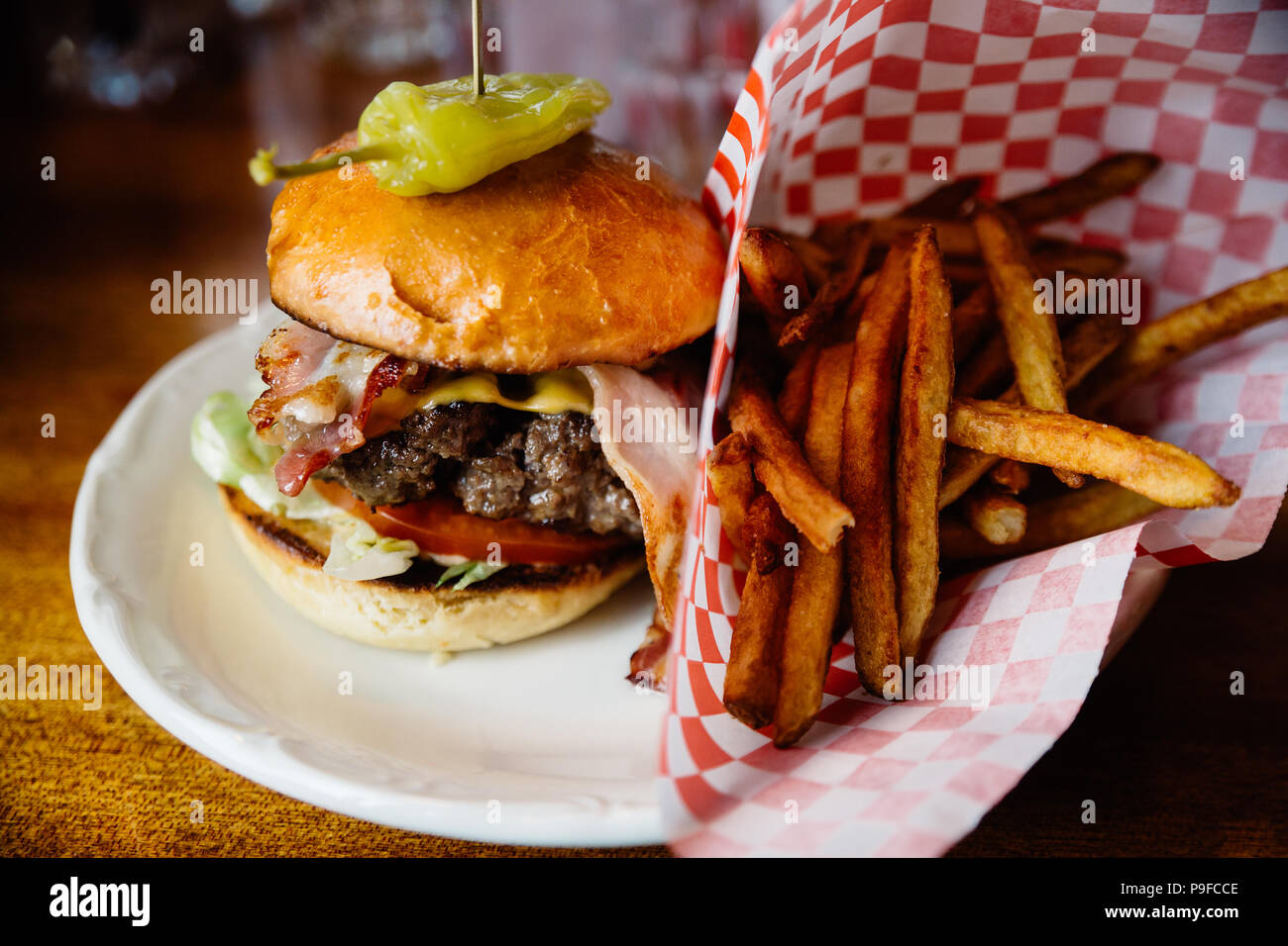 Burger with bacon, cheese and jalapeno pepper and french fries on the side. - Stock Image