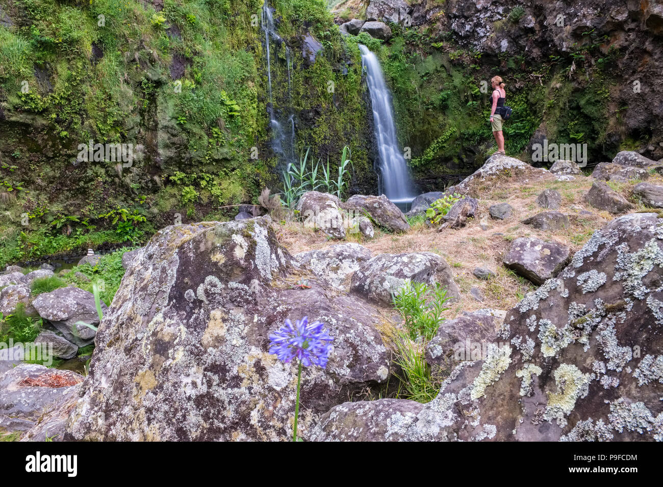 A woman walker at a waterfall on the north coast  of Sao Miguel, The Azores - Stock Image