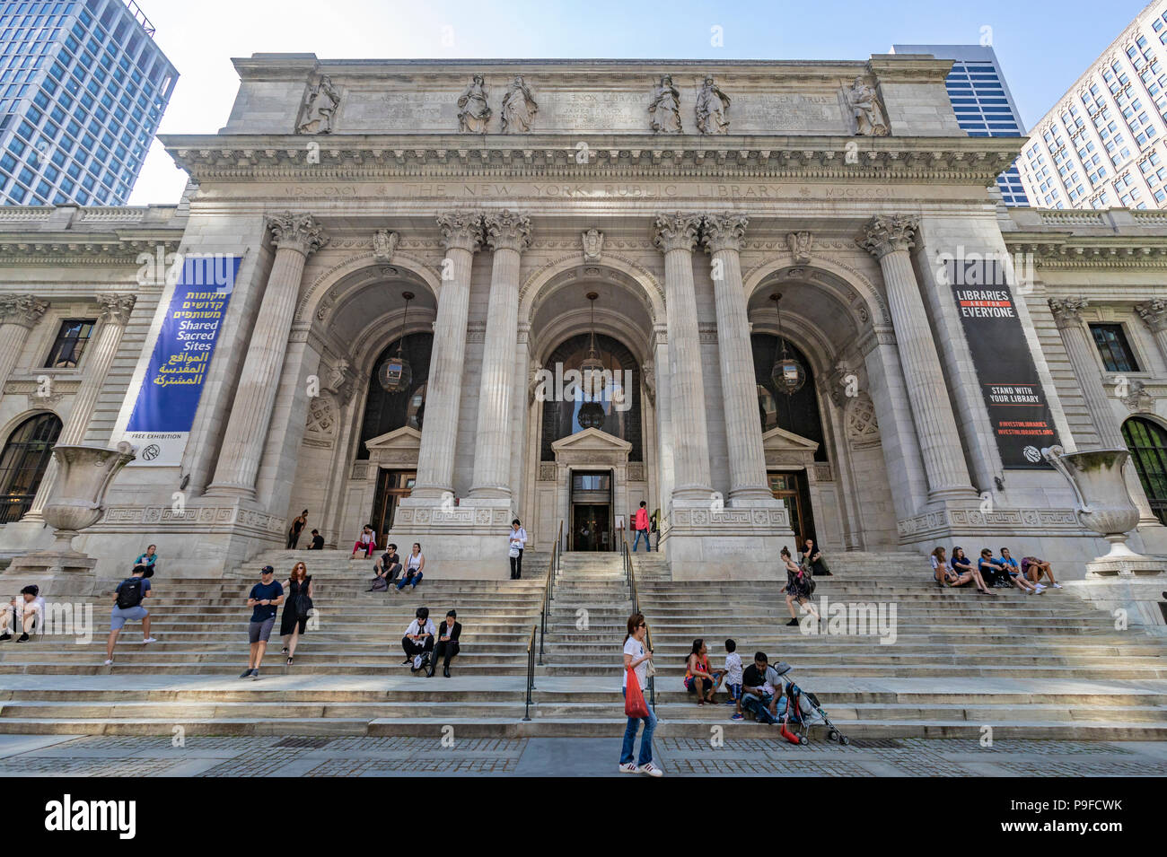 Exterior View of the New York Public Library on 42nd Street in Manhattan, New York City and people sitting on the steps. - Stock Image