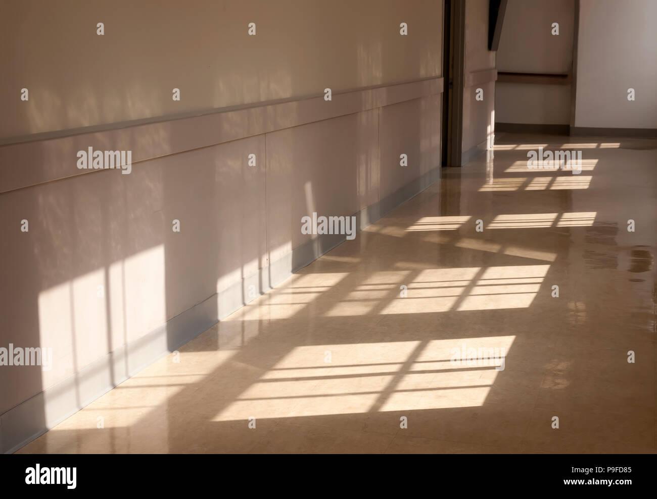 Sunlight shining through windows onto a hallway floor. - Stock Image