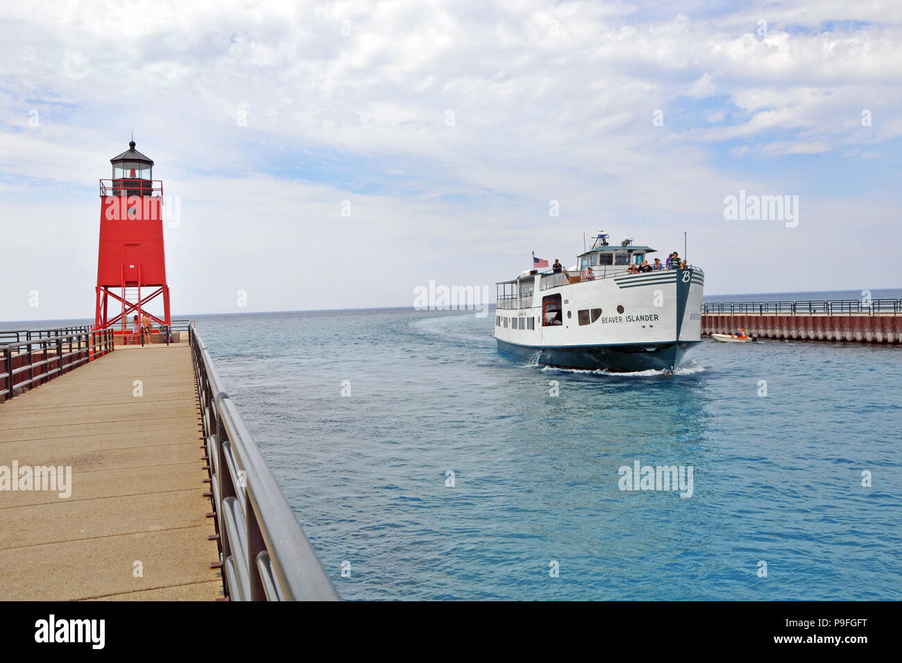 Beaver Islander ferry passes the Charlevoix South Pier Lighthouse on the Island Lake Outlet going from Lake Michigan to Charlevoix Lake (Michigan). - Stock Image